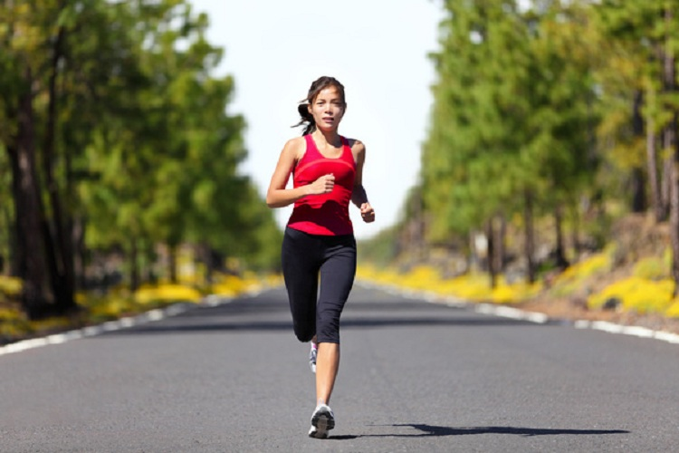 Sport fitness running woman jogging during outdoor workout. Beautiful young female athlete runner training for marathon on forest road in spring or summer. Mixed race Asian woman fitness model.